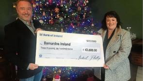 Michael Flatley presents Mary Gamble of Barnardos with cheque after auction